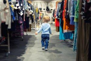 Kind im Kleidergeschäft